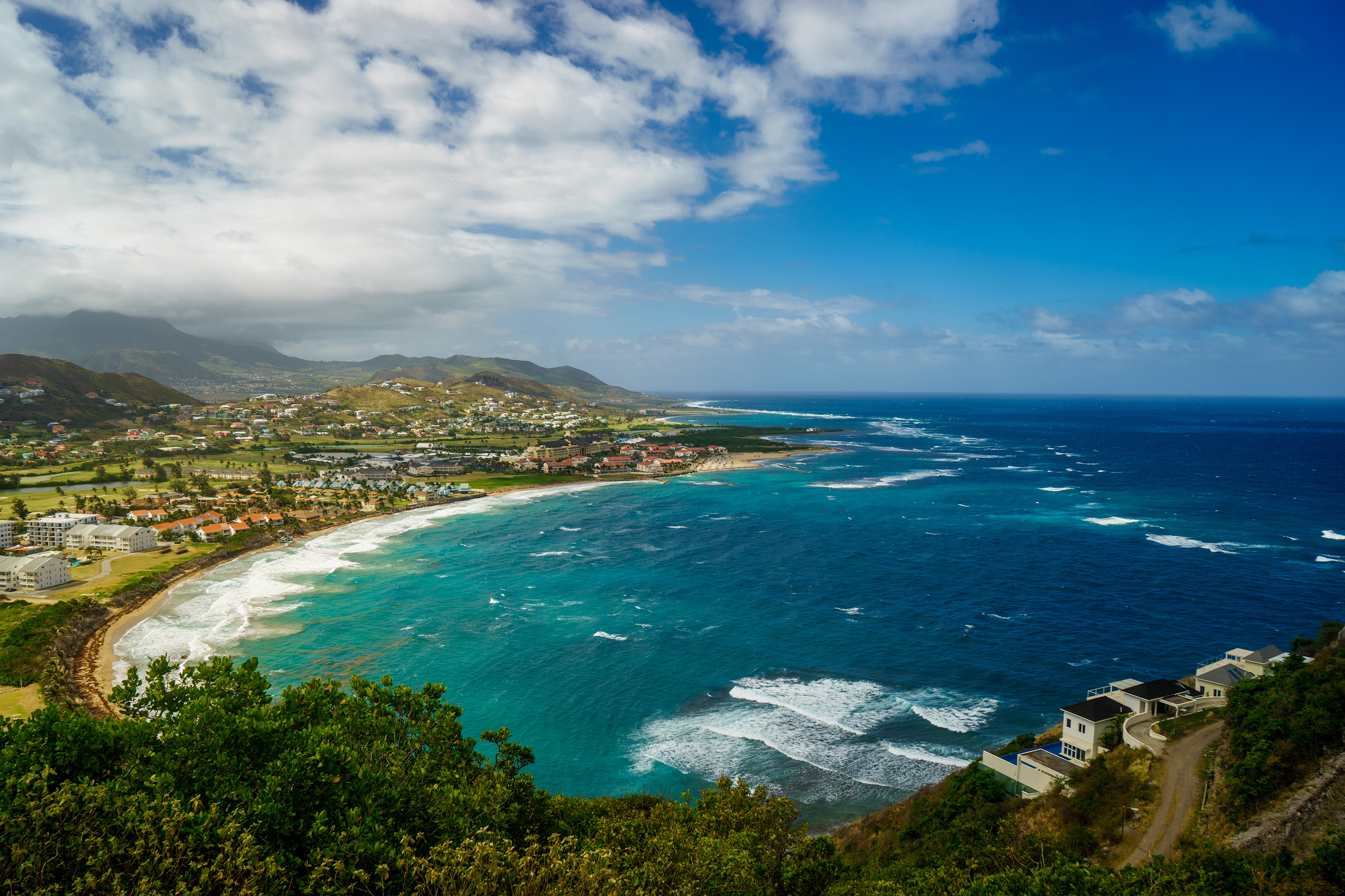 view-st-kitts-island-with-residential-area-beach-foreground-lush-green-hills